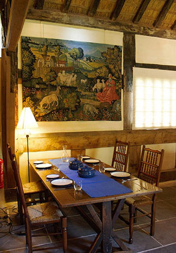 dining table beneath a replica C15th. tapestry.